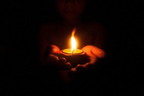 Hände halten eine Kerze in der Dunkelheit